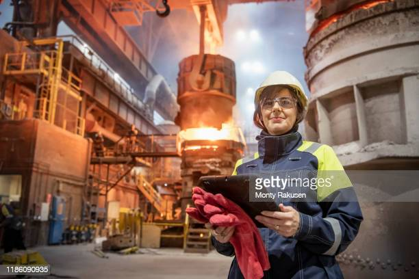 portrait of female steelworker during steel pour in steelworks - occupation stock pictures, royalty-free photos & images