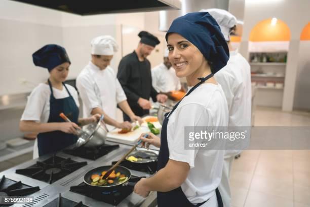 Retrato de estudante num Instituto de culinária olhando para câmera sorrindo