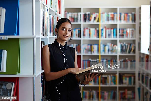 Portrait of female student holding book in library