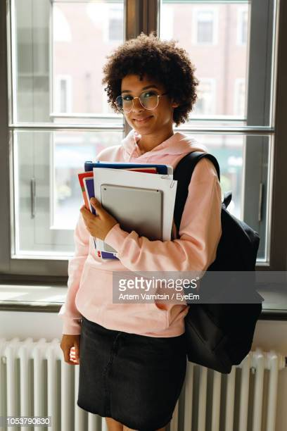 portrait of female student holding books against window - female high school student stock pictures, royalty-free photos & images