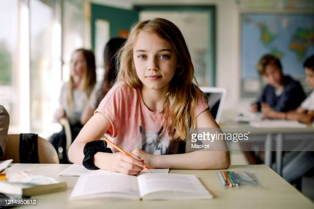 portrait of female student writing in book while sitting at table in classroom - mädchen stock-fotos und bilder