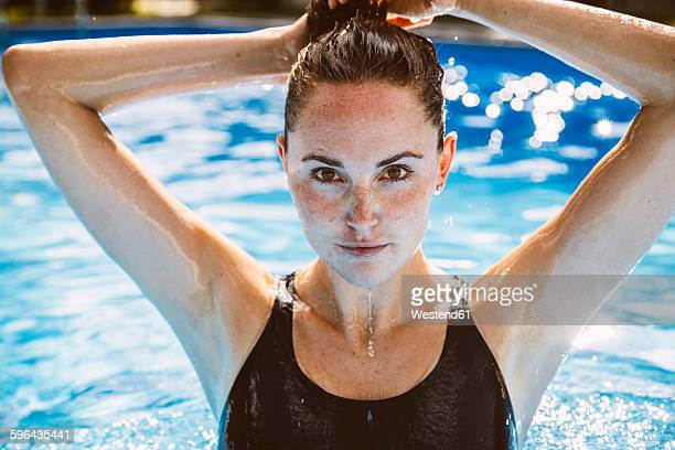 portrait of female swimmer fixing her hair while standing in swimming pool - schwimmen stock-fotos und bilder