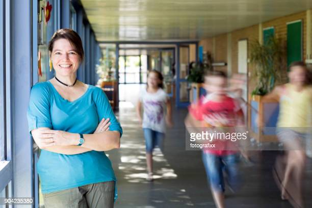 portrait of female teacher, leaning at corridor wall, running children in background - teacher stock pictures, royalty-free photos & images