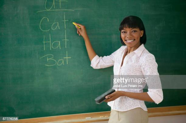 portrait of female teacher pointing to words on chalk board - spelling stock pictures, royalty-free photos & images