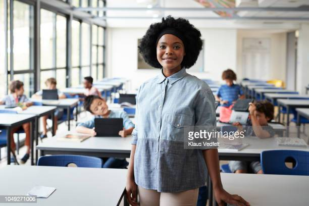 portrait of female teacher standing in classroom with students in background - lehrkraft stock-fotos und bilder