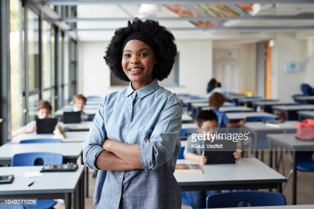 portrait of female teacher standing in classroom with students in background - rolled up sleeves stock pictures, royalty-free photos & images