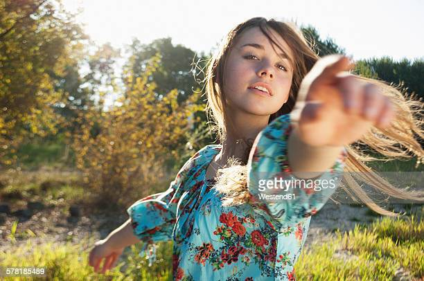 Portrait of female teenager dancing on a meadow