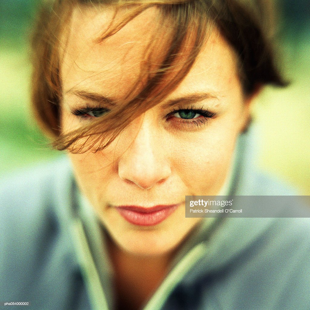 Portrait of female teenager looking into camera with hair in her eyes, close-up : Stockfoto