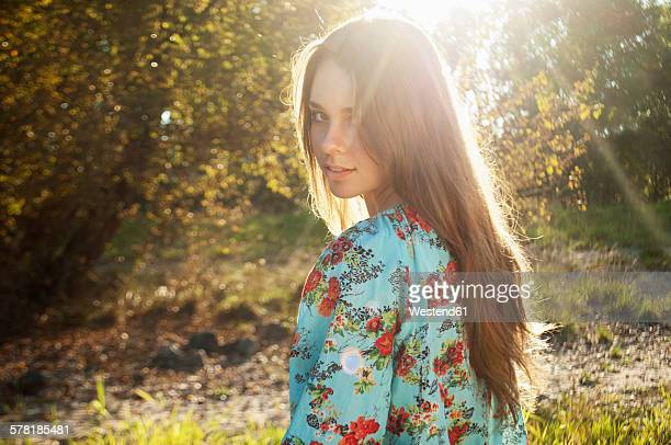 portrait of female teenager viewing over her shoulder at backlight - chemisier photos et images de collection