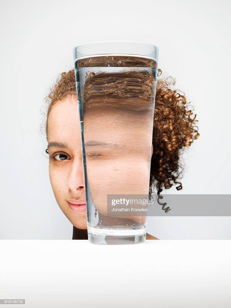 Portrait of female through glass of water : Stock Photo