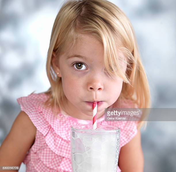 Portrait of female toddler blowing bubbles in milk through drinking straw