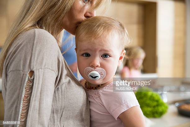 Portrait of female toddler in mothers arms in kitchen