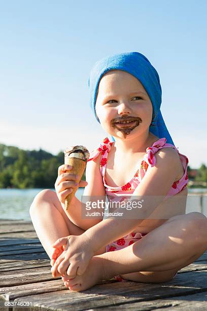 Portrait of female toddler on pier eating chocolate ice cream cone, Lake Seeoner See, Bavaria, Germany