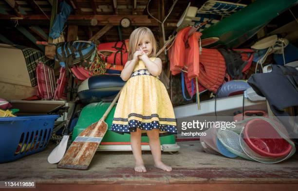 portrait of female toddler standing at front of storage garage - heshphoto bildbanksfoton och bilder