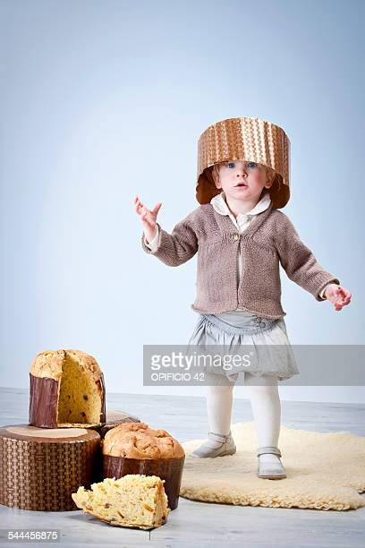 Portrait of female toddler wearing pannetone cake case as hat