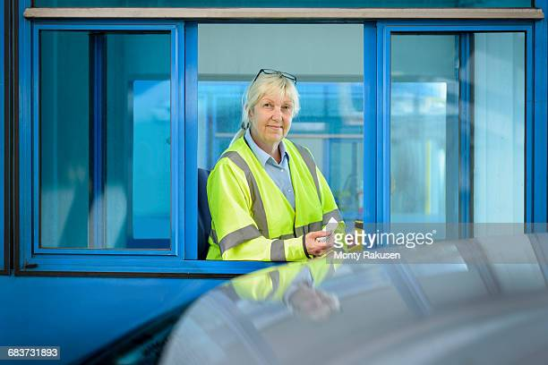 Portrait of female toll collector at toll booth on bridge