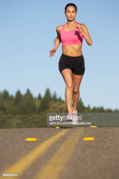 Portrait of female track runner on highway