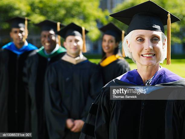 portrait of female university graduate with others in background (focus on foreground) - graduation background stock pictures, royalty-free photos & images