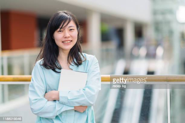 portrait of female university student while holding textbook - japanese ethnicity stock pictures, royalty-free photos & images