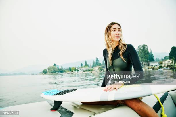 Portrait of female wakesurfer on stern of boat during early morning surf session