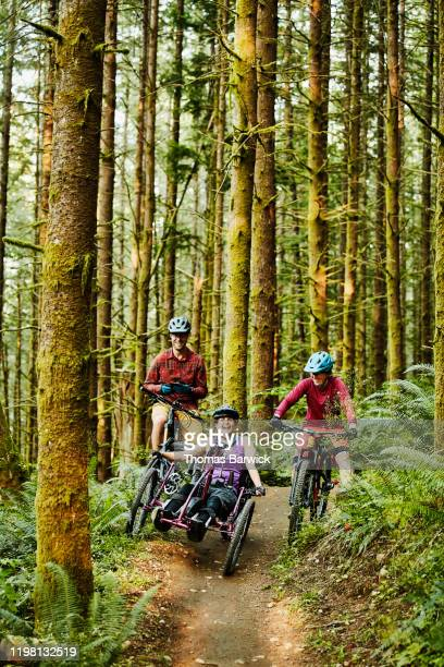 portrait of female wheelchair athlete and friends on mountain bike trail - forward athlete stock pictures, royalty-free photos & images