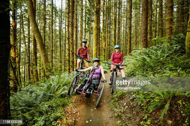 portrait of female wheelchair athlete and friends on trail while riding mountain bikes - forward athlete stock pictures, royalty-free photos & images