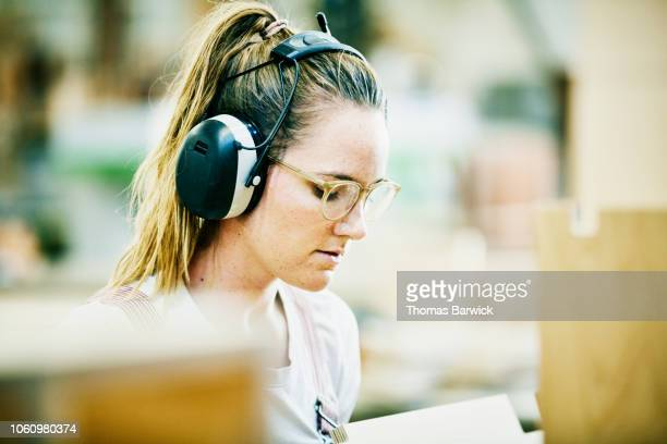 portrait of female woodworker working in cabinet shop - ear protection stock pictures, royalty-free photos & images