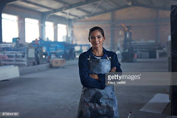 portrait of female worker at factory - orgoglio foto e immagini stock