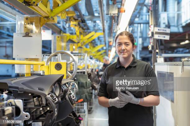 portrait of female worker on dashboard assembly line in car factory - manual worker stock pictures, royalty-free photos & images