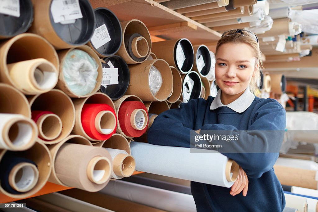 Portrait of female worker with fabric rolls in roller blind factory : Stock Photo