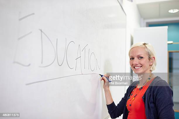 Portrait of female writing on white board