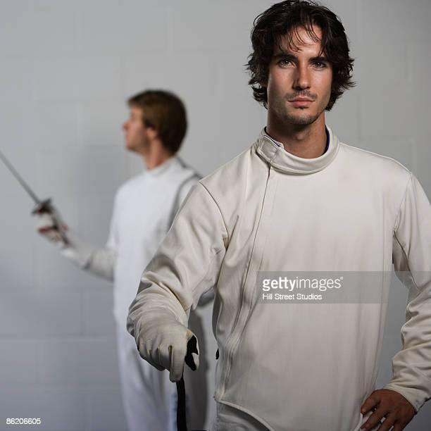 Portrait of fencers holding fencing foils