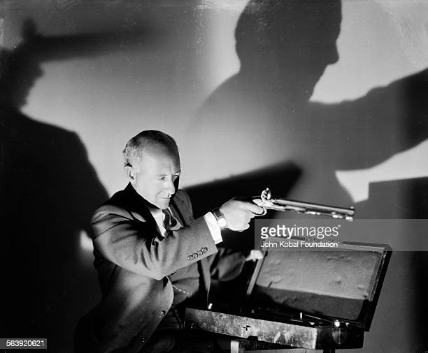 Portrait of filmmaker Cecil B DeMille inspecting a prop from the film 'The Squaw Man' for MGM Studios 1930