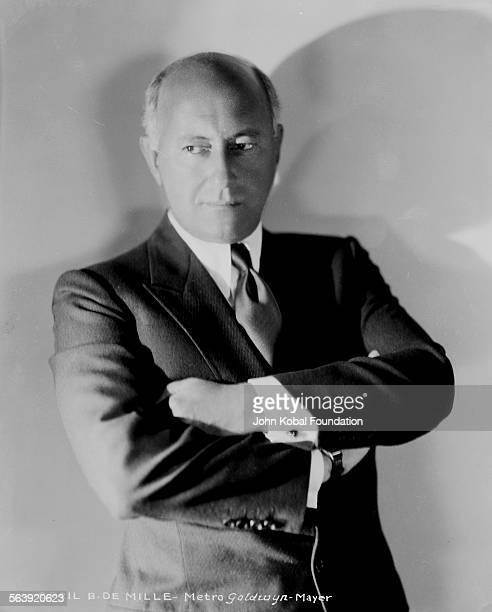 Portrait of filmmaker Cecil B DeMille with his arms folded for MGM Studios 1930