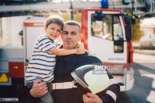 portrait of firefighter holding little boy on hands - firefighter stock pictures, royalty-free photos & images