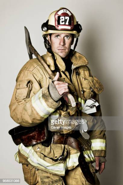 portrait of firefighter holding shovel standing against white background - capacete de bombeiro - fotografias e filmes do acervo