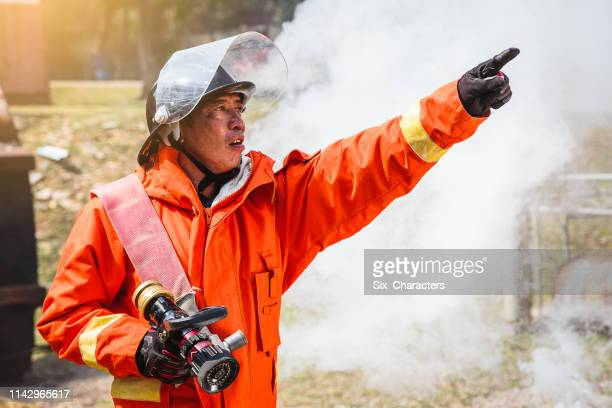 portrait of firefighter man in fire operation at wall of smoke, firefighters extinguish burning warehouse - hand sign stock pictures, royalty-free photos & images