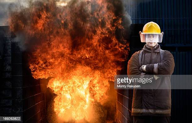 Portrait of firefighter standing by domestic fire simulation in training facility