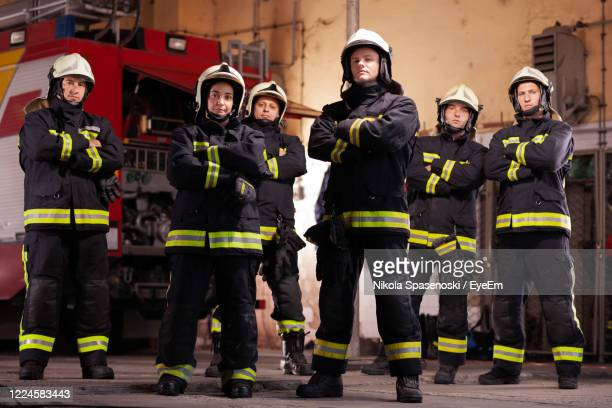 portrait of firefighters standing in fire station - 救助隊 ストックフォトと画像
