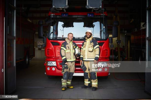 portrait of firefighters standing in front of fire engine at fire station - fire station stock pictures, royalty-free photos & images