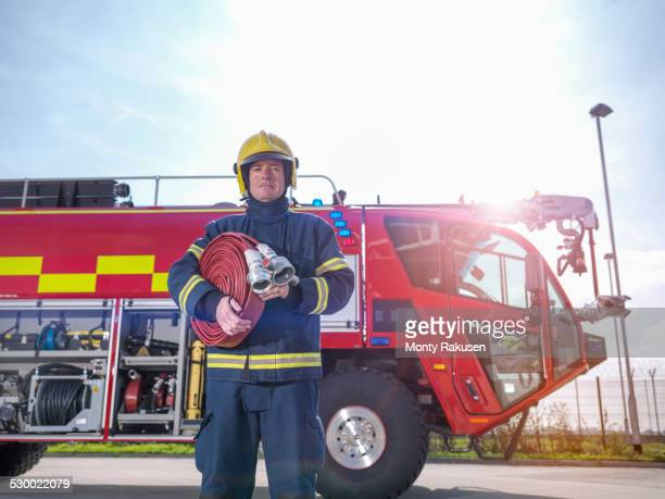 portrait of fireman in front of fire engine in airport fire station - fire station - fotografias e filmes do acervo