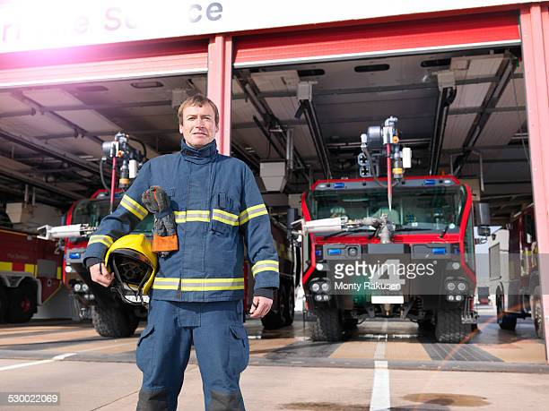 portrait of fireman in front of fire engines in airport fire station - fire station - fotografias e filmes do acervo