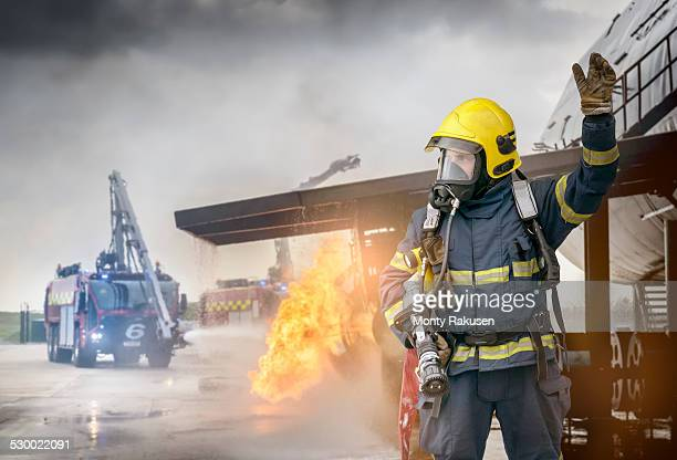portrait of fireman in front of simulated fire at airport training facility - firefighter stock pictures, royalty-free photos & images
