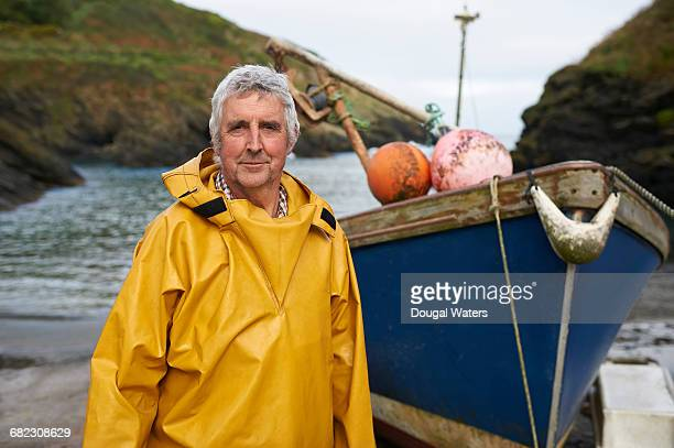 portrait of fisherman and boat on sea shore. - dougal waters stock pictures, royalty-free photos & images