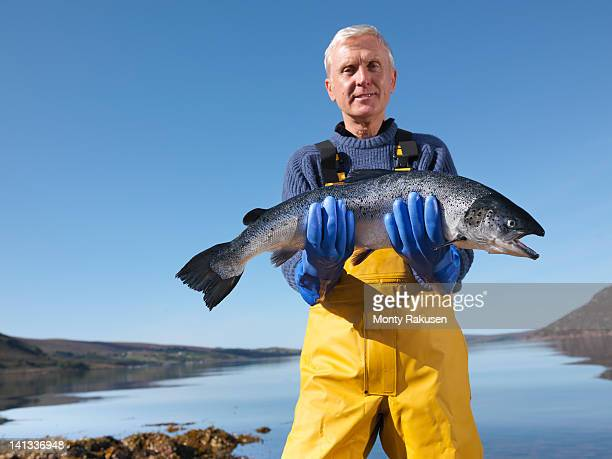 Portrait of fisherman standing in loch holding freshly caught salmon