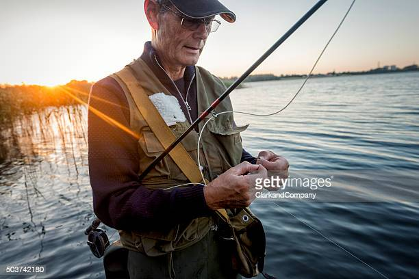 portrait of fisherman tying a fly on stege nor denmark - hobbies stock pictures, royalty-free photos & images