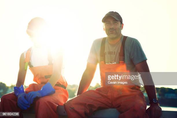 portrait of fishermen sitting at trawler - fisherman stock pictures, royalty-free photos & images