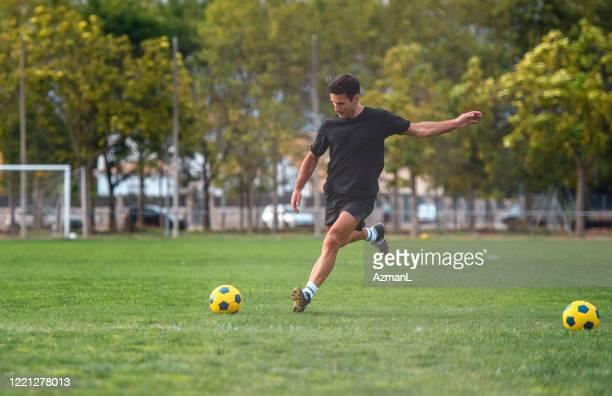 フィット成熟した男性サッカー選手の肖像画キックを練習 - トレーニングドリル ストックフォトと画像