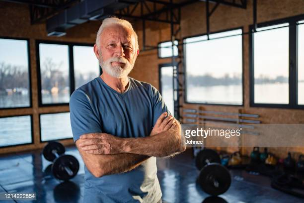 verticale de l'homme aîné d'ajustement dans la gymnastique - plan moyen angle de prise de vue photos et images de collection