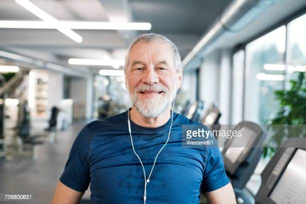 Portrait of fit senior man with earphones in gym